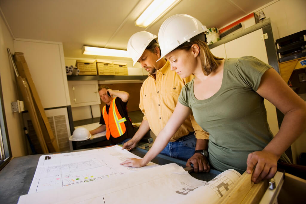 Workers Reviewing Blueprints --- Image by © Kelly Redinger/Design Pics/Corbis